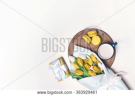 Coffee Cup, Yellow Tulip Flowers And Yellow Macarons On Pastel Table. Top View. Greeting For Womans