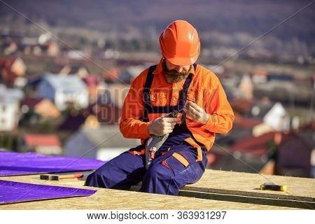 Flat Roof Installation. Man Hard Hat Working Outdoor Landscape Background. Building House. Install V