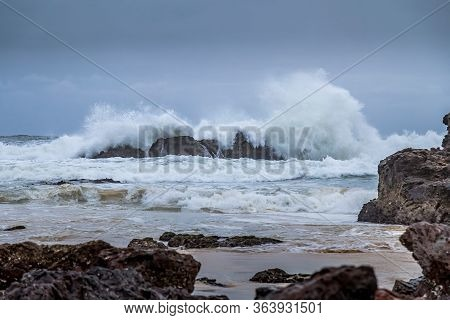 Rocks Next To The Beach Of The Camel Rock Bay In New South Wales, Australia At A Cloudy And Windy Da