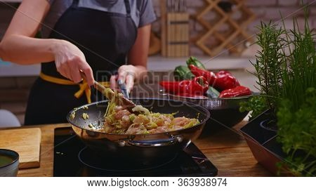 Woman cooking frying chicken meat in wok pan on kitchen table. Closeup hands. Cosy dark room. Real, authentic cooking.