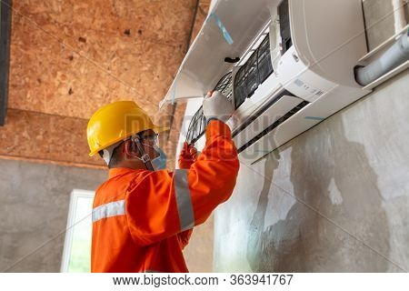 Asian Male Technician Wear Safety Clothes Install Air Conditioner Indoors And Wear Protective Masks