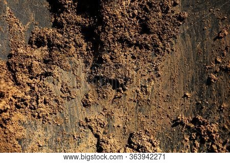Off road, or farming.  substantial amount of dirt on black metal plate close-up.