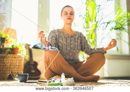 Beautiful Woman Doing Yoga At Home In Sunny Day. Crystal And Aroma Stick Burn. Camera Out Of Focus.