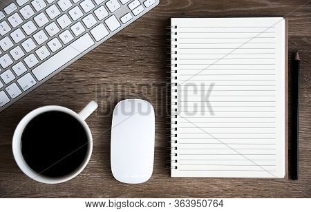 A High Angle View Of A Home Office Desk With Keyboard, Coffee, Mouse And Spiral Notebook With Lined
