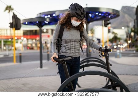 Caucasian woman out and about in the city streets during the day, wearing a cycling helmet and a face mask against covid19 coronavirus, parking her bicycle at a cycle stand