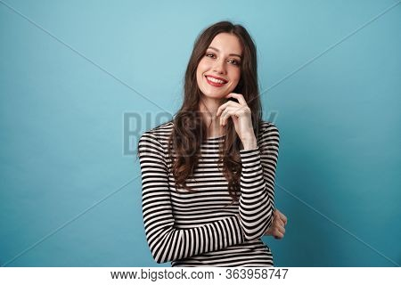 Photo of joyful nice woman in striped sweater smiling and looking at camera isolated over blue wall