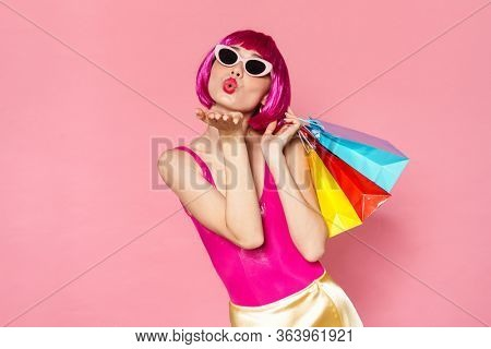 Image of young girl wearing wig and sunglasses doing air kiss while holding shopping bags isolated over pink background