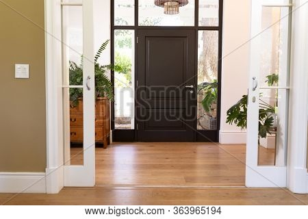 The insides of a house, hallway, closed front door, with hanging lamp and house plants, on a sunny day