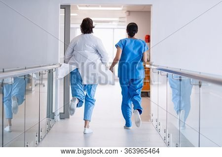 Rear view of nurse and doctor running in hospital corridor
