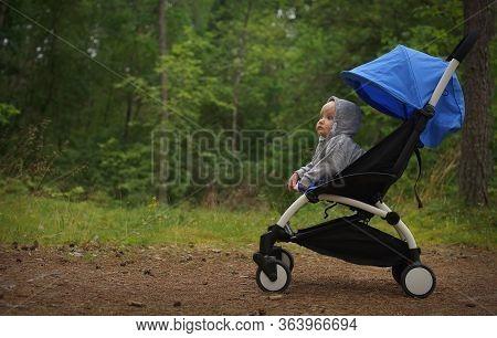 Side Portrait Of Small Thoughtful Child In Sweatshirt Hood On Head Sitting In Baby Stroller On Backg
