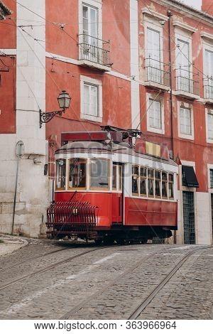 Lisbon, Portugal. Vintage Red Retro Tram On Street Tramline In Alfama District Of Old Town. Popular