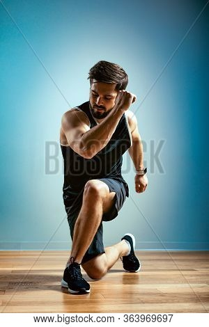 A Man Does Functional Exercises In The Gym On A Gray Background. Fitness Concept, Sports Body, Body