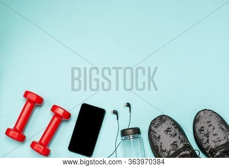 Flat Lay Of Sports Equipment For Fitness On A Blue Background. Sports Shoes, Bottle Of Water, Dumbbe