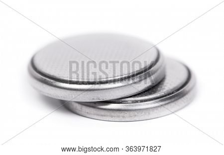 Flat lithium round button cell battery isolated over white background
