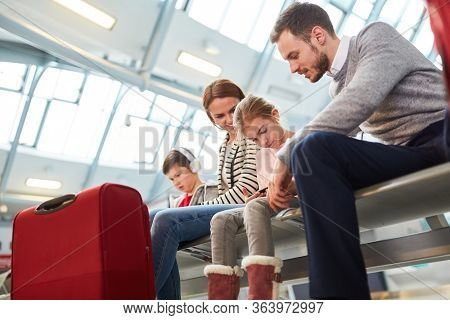 Family with children in airport terminal waiting area waiting for the flight on vacation