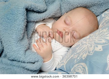 Adorable little baby sleeping peacefully on a blanket