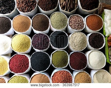 Top view on a assortment of various type of uncooked spice, beans, seeds, lentils, chickpeas