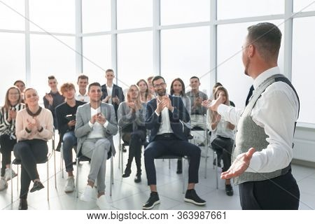 smiling speaker standing in front of an applauding audience