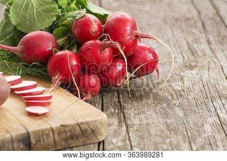Harvested Bunch Of Fresh Raw Red Radishes With Leaf Near Cutting Board On Sliced Radish. Healthy Org