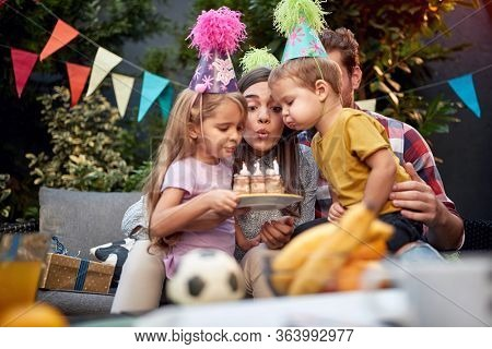 gathered young family blowing birthday candles together. birthday, togetherness