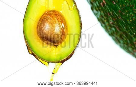 Freeze motion of sliced avocado with splashing oil isolated on white background