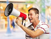 Portrait Of A Handsome Young Man Shouting With Megaphone, Outdoor poster
