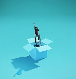 Man On A Ladder Looking Through Binoculars . Think Outside The Box Concept .