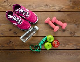 Fitness Concept With Fruits, Dumbbells, Measuring Tape, Bottle Of Water And Sport Shoes On Wooden Te