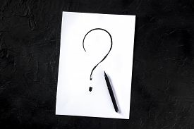 Question Mark, Written In Ink On A Piece Of Standard Office Paper, Shot From The Top On A Black Back