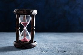 Time Concept. An Hourglass With Sand Falling Through, On A Dark Background With Copy Space