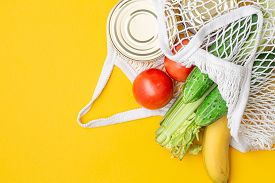 Delivery Food. Food Items In A String Bag On A Yellow Background. Canned Food, Tomatoes, Cucumbers,