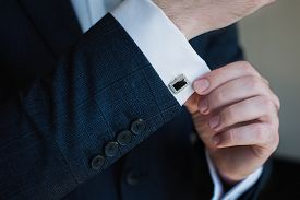 Elegant Fashion Man Looking At His Cufflinks While Fixing Them. Handsome Groom Dressed In Black Form