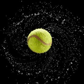 Tennis Ball Spinning Fast Splashing Water Drops In A Circle On Black Background.