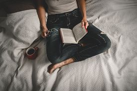 Woman Reading Book At Home On Bed. Woman Relaxing On Bed At Home. Hipster Lifestyle. Beautiful Woman