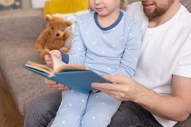 Family of young father and his adorable little daughter in blue pajamas reading interesting book while relaxing at home before sleep