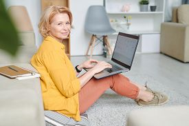 Happy mature blond woman with laptop on her knees sitting on the floor and carrying out working points during remote work on quarantine