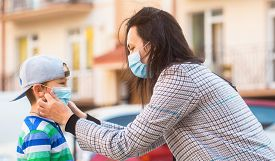 Mother, Child Wear Facemask During Coronavirus, Flu Outbreak. Mom Puts A Medical Mask On Her Son. Ch