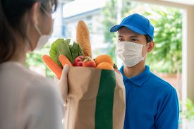 Asian Delivery Man Wearing Face Mask And Glove With Groceries Bag Of Food, Fruit, Vegetable Give To