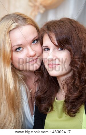 Two Caucasian Young Women Standing Cheek To Cheek. Close Up Of Faces
