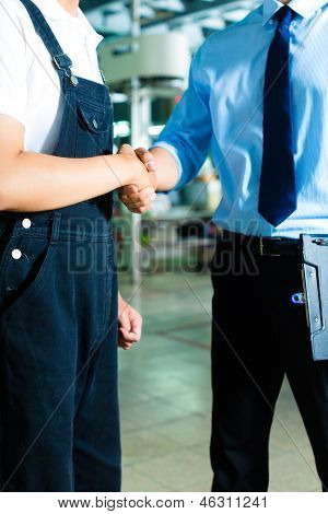 Worker or production manager and owner, ceo or controller shake hands in a factory