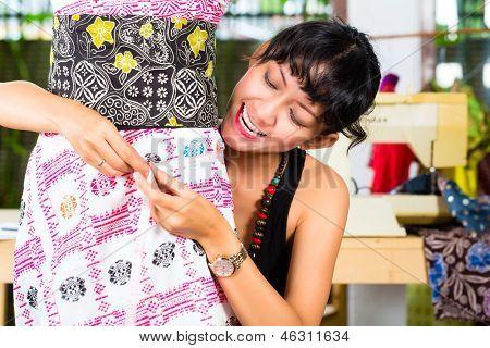 Freelancer - Fashion designer working at home on a design or draft, she takes measure on a dressmaker's dummy