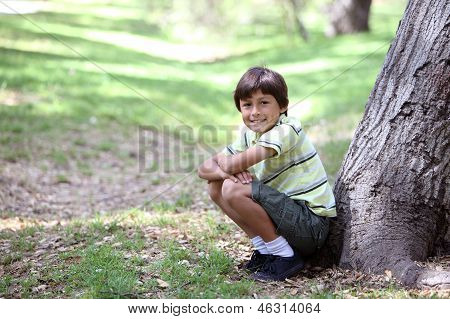 Young boy under tree