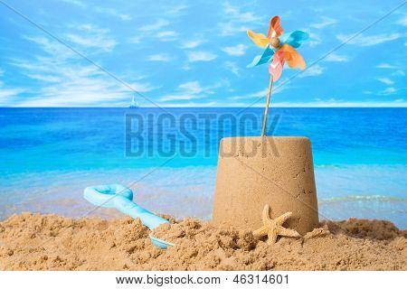Sandcastle with windmill on summer beach