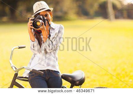 lächelnd junge Frau, die mit einer Kamera Foto im freien im Park zu machen