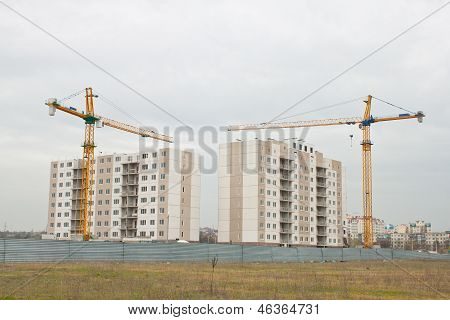 Building Cranes above the unfinished apartment house.