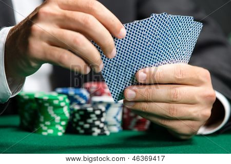 Gambler playing poker cards with poker chips on the table. Risky entertainment of gambling