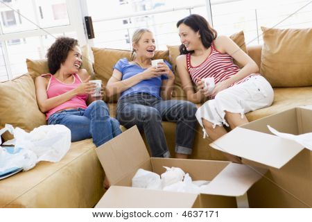 Three Girl Friends Relaxing With Coffee By Boxes In New Home Smiling