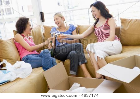 Three Girl Friends Toasting Champagne By Boxes In New Home Smiling