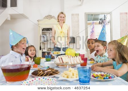 Young Children At Party Sitting At Table With Mother Carrying Cake And Smiling