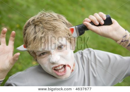 Young Boy With Scary Halloween Make Up And Plastic Knife Through Head